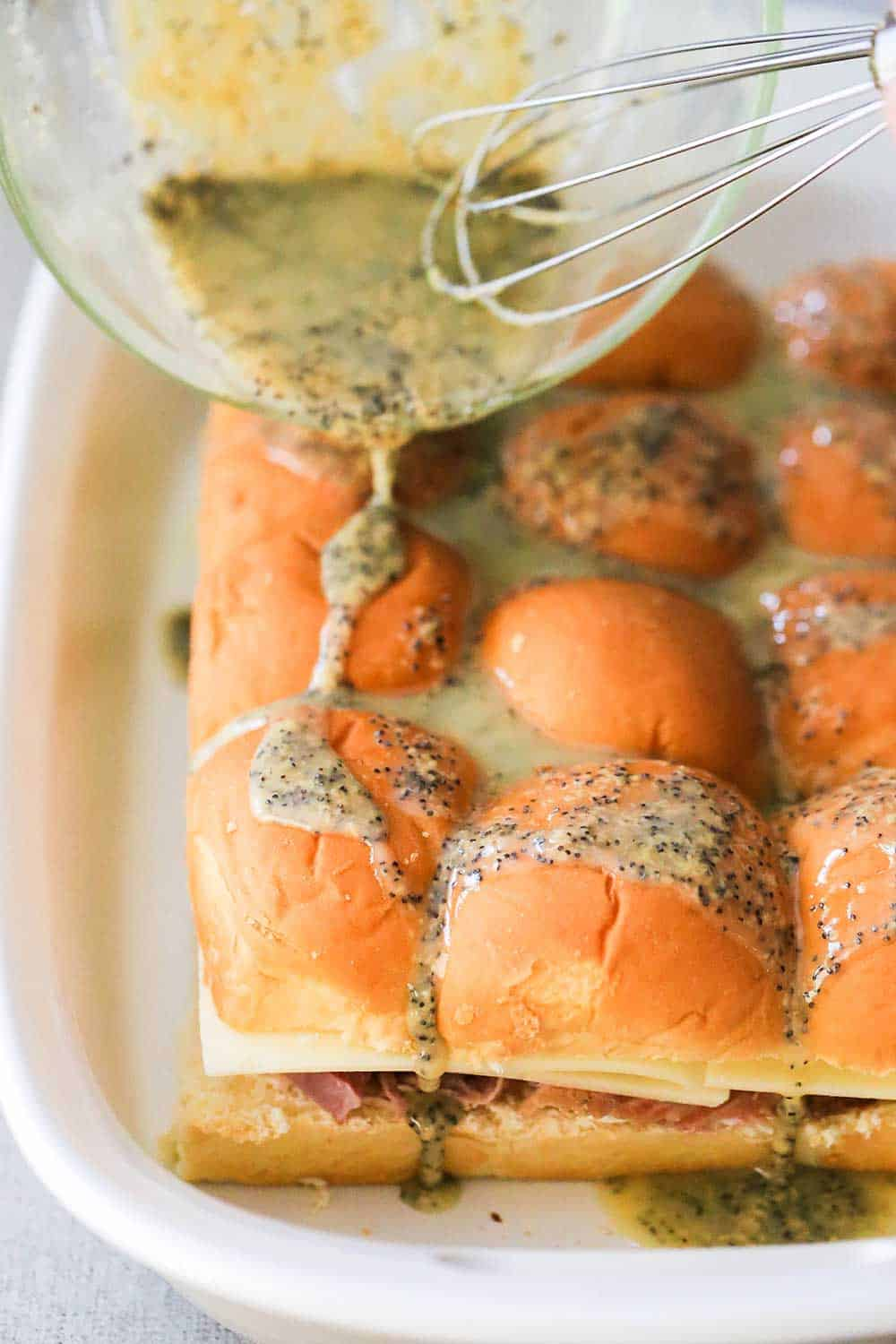 A hand pouring a butter sauce over the tops of ham and Swiss sliders in a white baking dish.