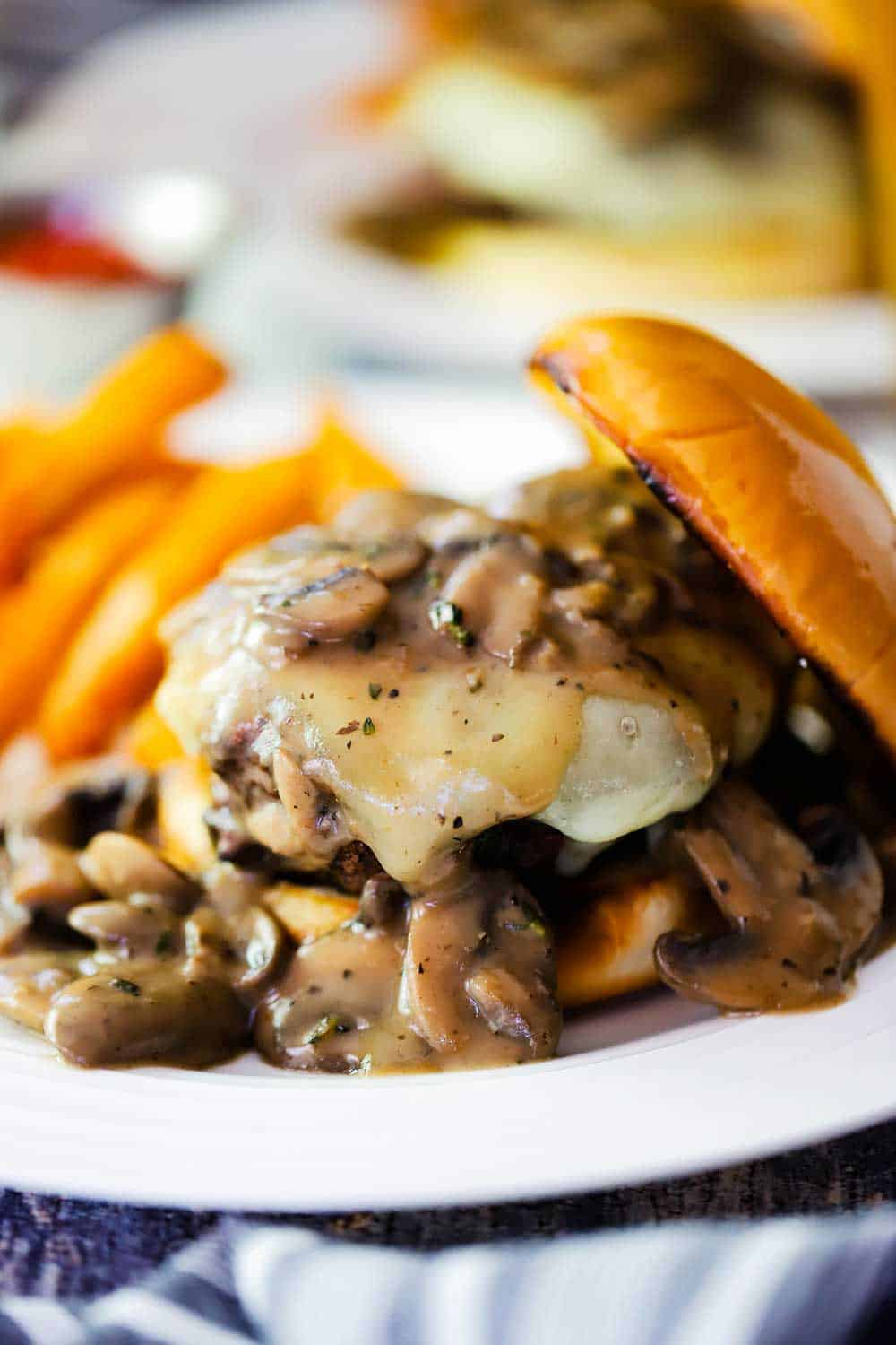 A close up view of a mushroom Swiss burger on a white plate with a pile of French fries next to it.