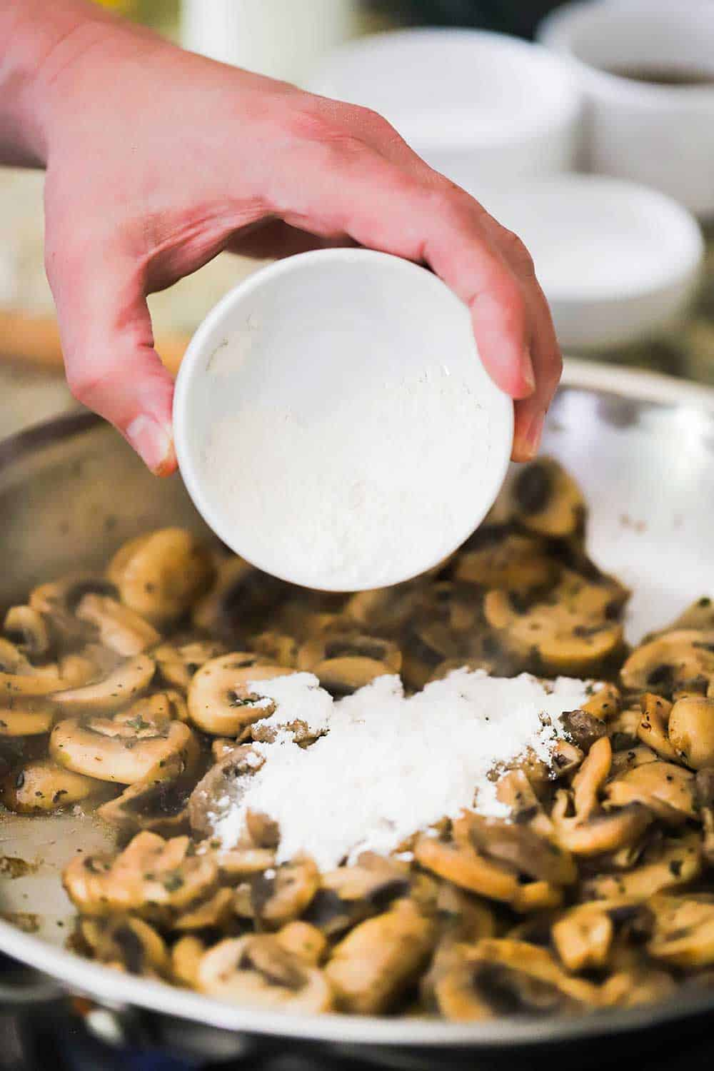 A hand sprinkling flour from a small bowl into a skillet filled with sautéed mushrooms.