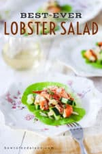 A mound of lobster salad with cucumber on a leaf of lettuce on a decorative plate next to a glass of white wine and a platter.