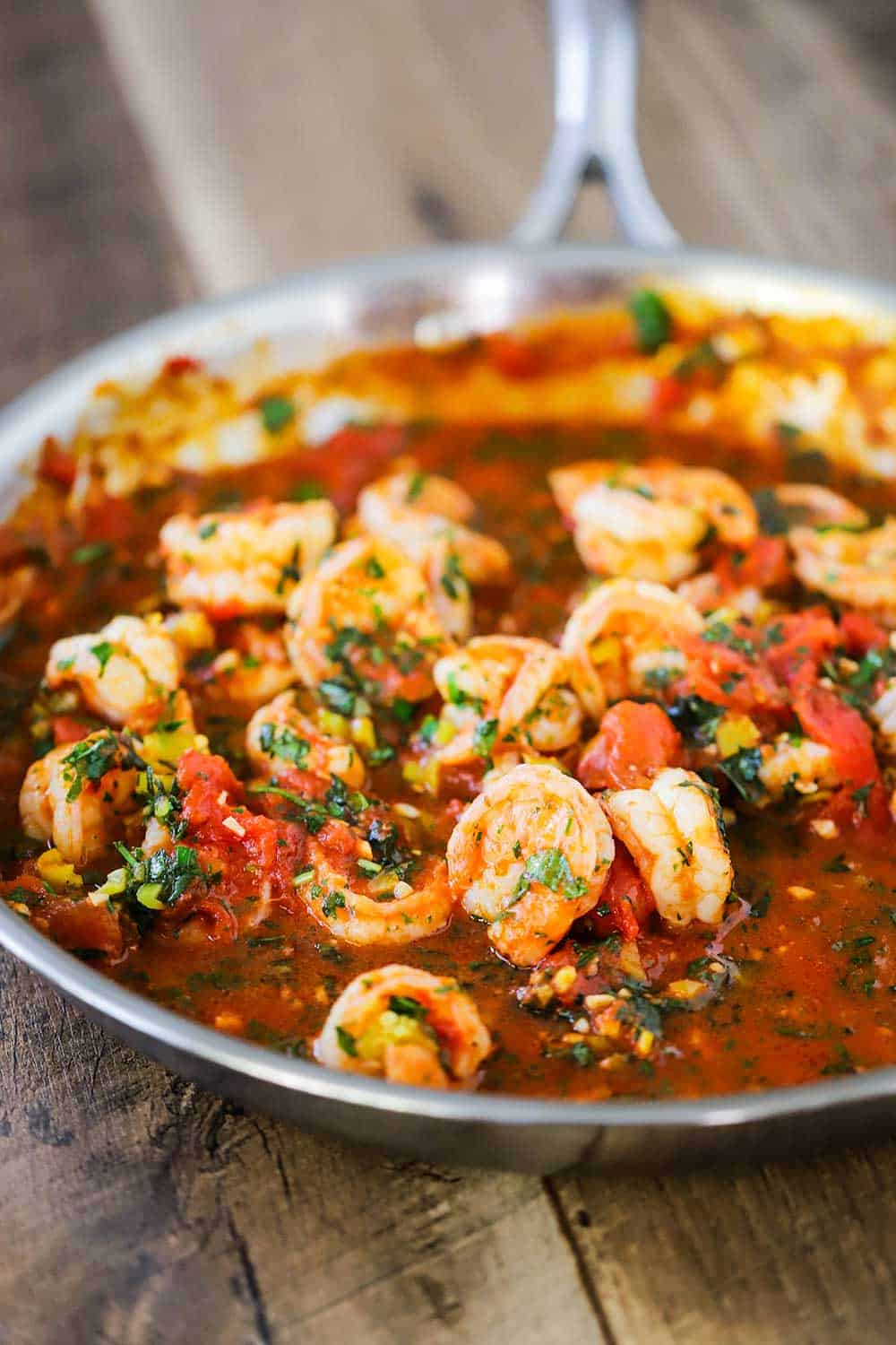 A large silver skillet filled with cooked shrimp fra diavolo sitting on wooden planks.