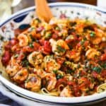 A large festive pasta bowl filled with shrimp fra diavolo with sliced Italian bread next to it and a glass of white wine.