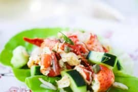 A close-up view of a lobster salad with cucumbers on a green leaf of lettuce on a decorative plate.