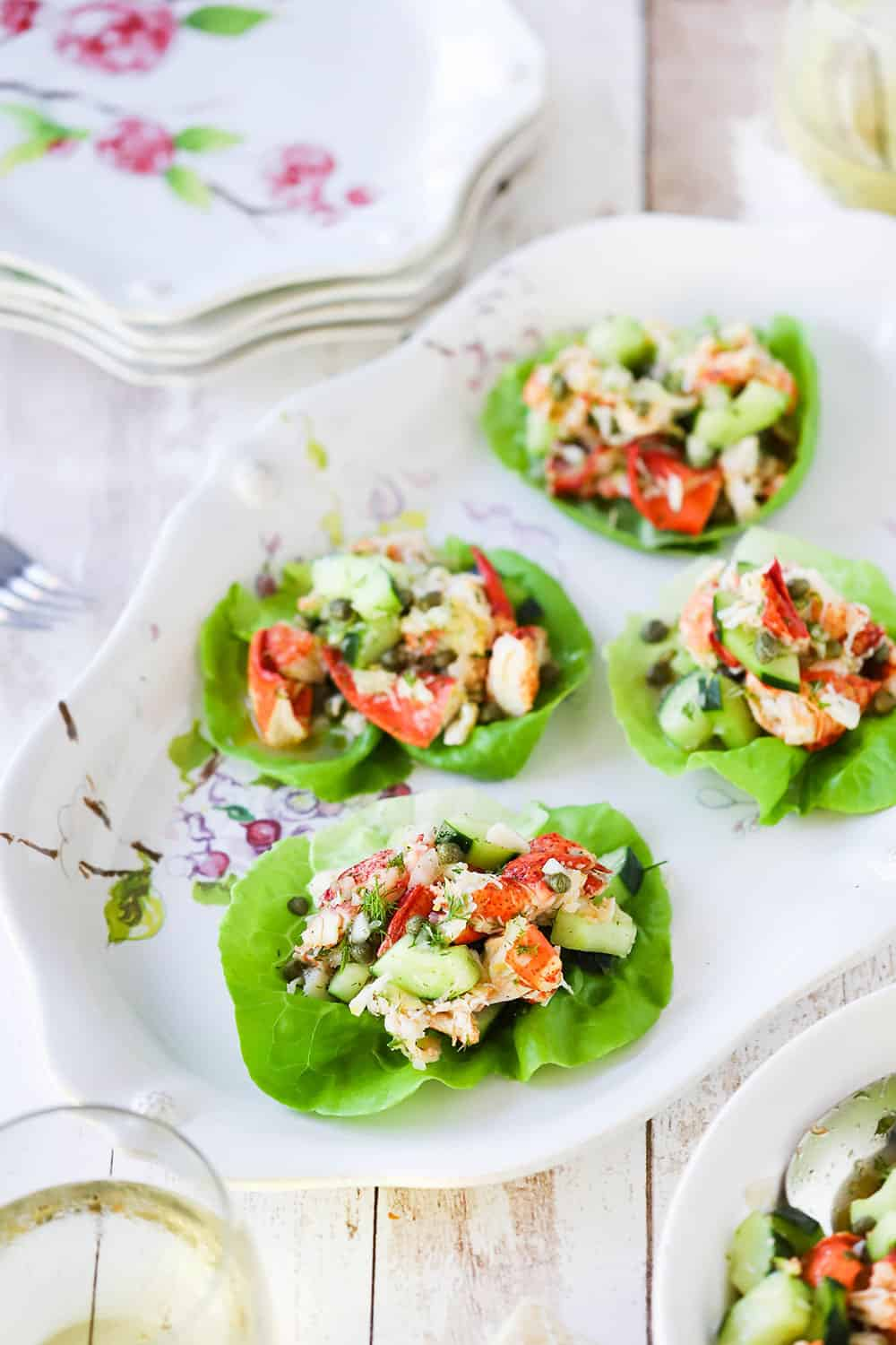A large decorative platter filled with 4 lettuce leafs topped with a lobster salad with cucumbers and herbs.