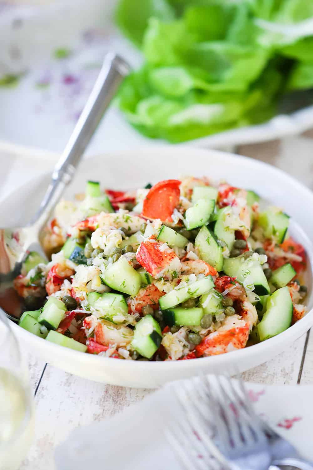 A white serving bowl filled with a lobster salad with cucumber and herbs with a large silver spoon in the salad.