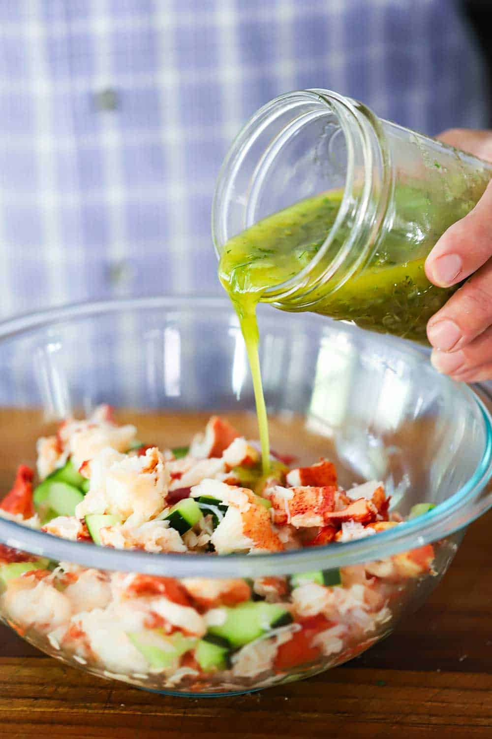 A person pouring a lemon vinaigrette from a mason jar into a glass bowl filled with chopped fresh lobster and cucumbers.