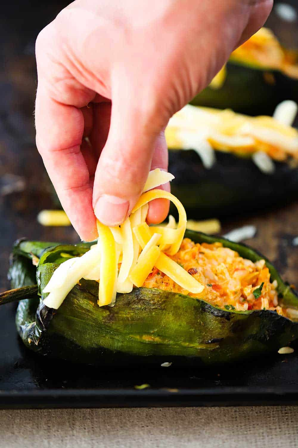 A hand sprinkling shredded cheddar cheese on top of stuffed poblanos on a baking sheet.