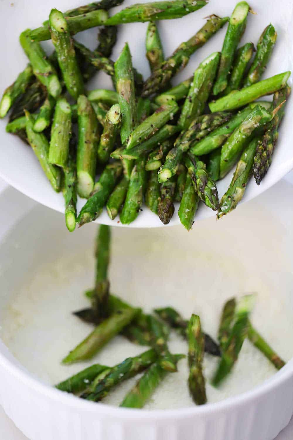 A plate filled with cut roasted asparagus pieces being dropped into a white souffle dish.