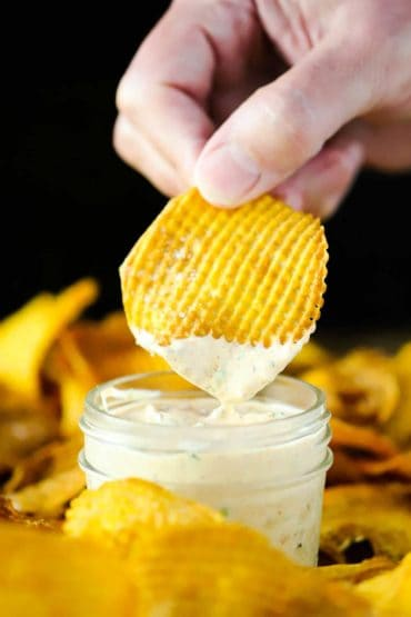 A hand dipping a cross hatch sweet potato chip into a small jar of kickin' remoulade sauce.