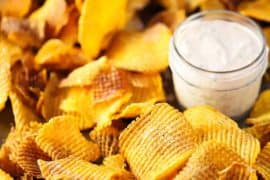 A large baking dish filled with cross hatch sweet potato chips with a small glass jar of spicy remoulade nestled into the chips.