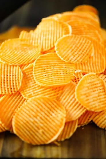 A stack of thinly slice sweet potato chips in a cross hatch style.