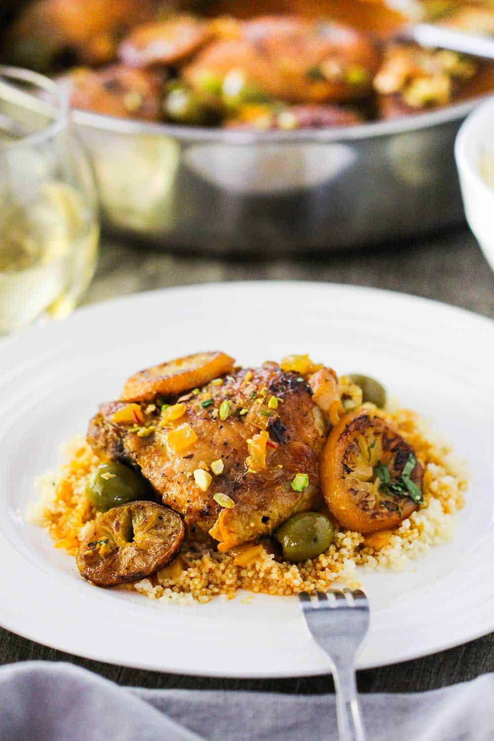 A white dinner plate with a serving of chicken tagine with preserved lemons and olives over a bed of couscous, all sitting next to a skillet filled with the chicken tagine.