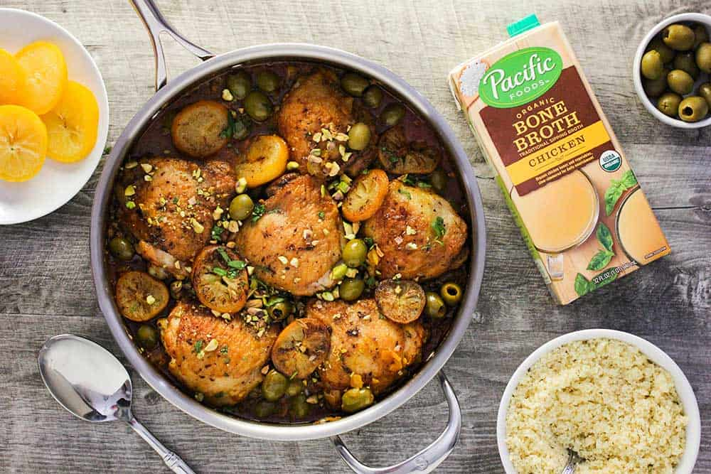 A large silver skillet filled with chicken tagine with preserved lemons and olives, next to a bowl of couscous and a box of Pacific Foods organic chicken broth.