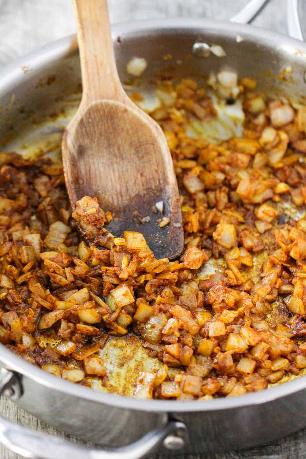 A skillet filled with sautéed onions and Moroccan spices with a wooden spoon in the middle.