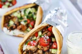 Two chicken gyros wrapped in foil on a white platter next to a small jar filled with tzatziki sauce with a spoon in, with a whole tomato and parsley in the background.