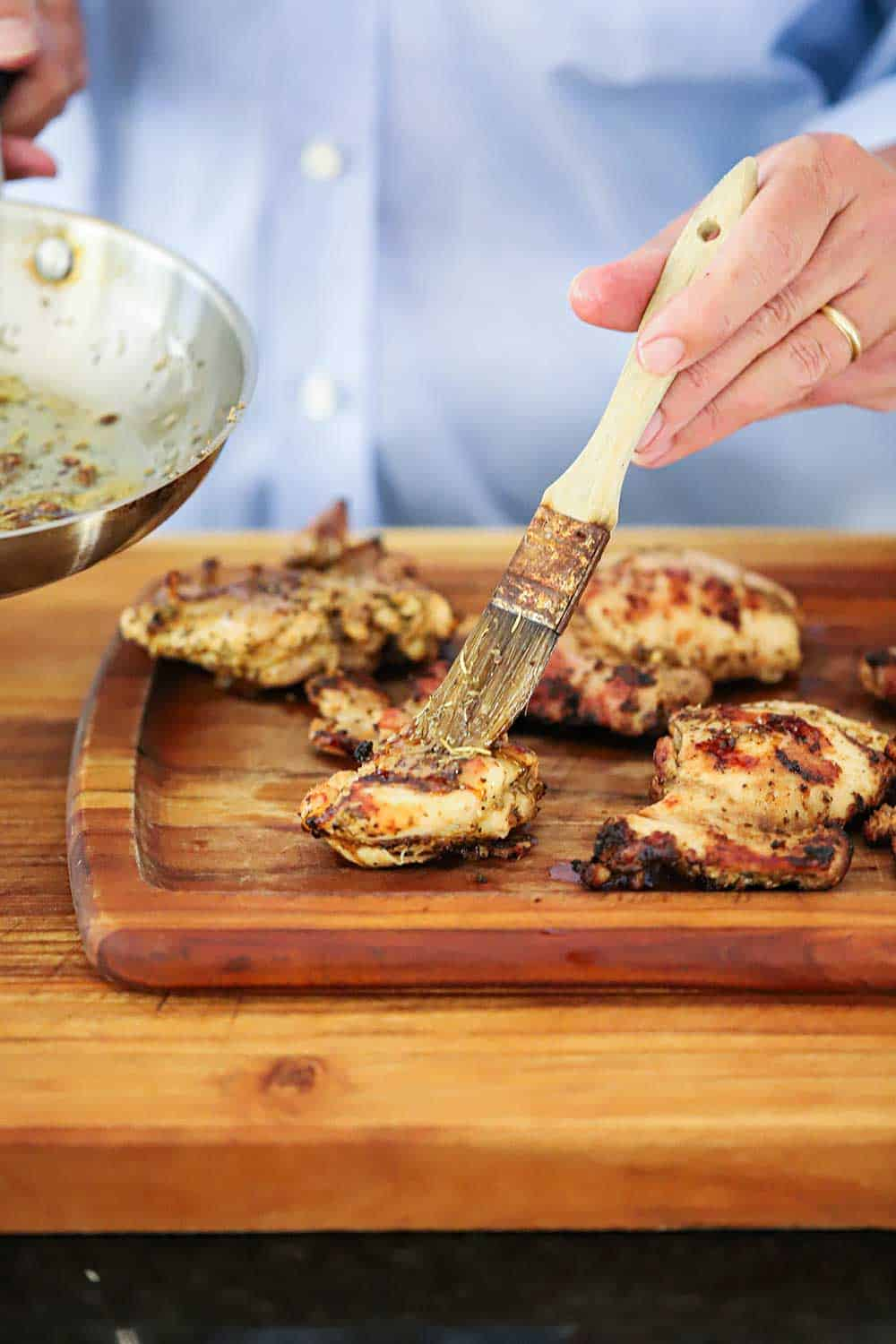 A hand brushing infused oil over grilled chicken thighs on a wooden cutting board.