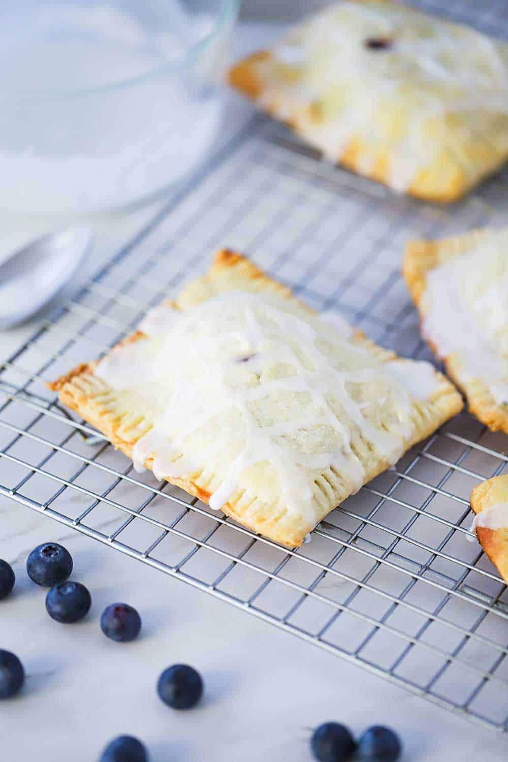 Homemade blueberry pop tarts on a baking rack with fresh blueberries and spoon sitting nearby.