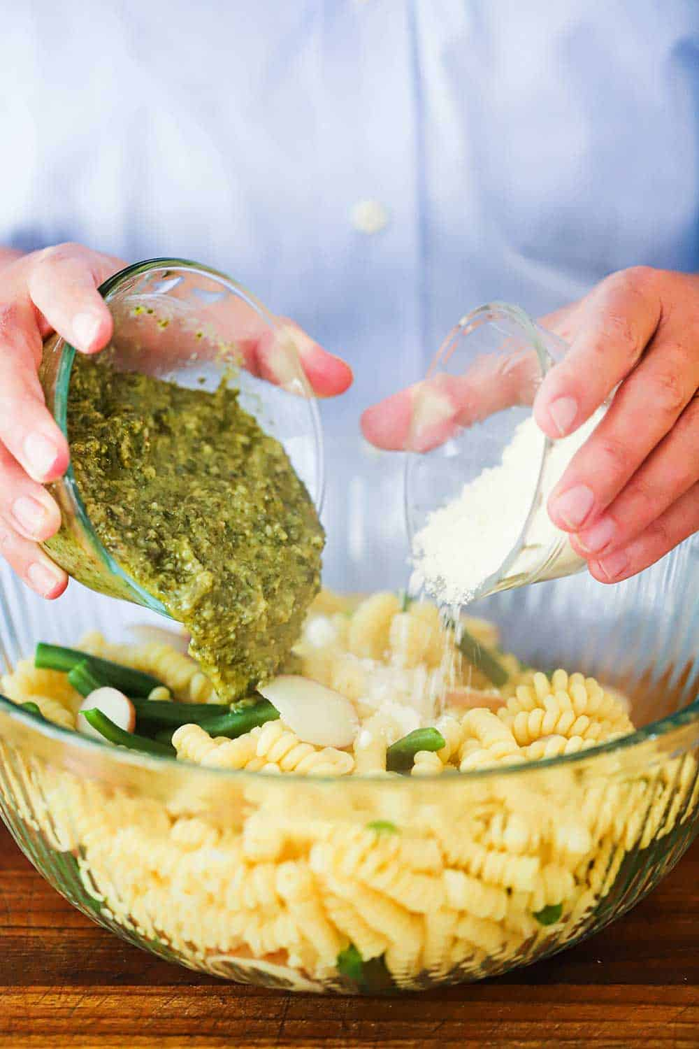 Two hands pouring a glass bowl of pesto sauce and another bowl of Parmesan cheese into a bowl of cooked fusili pasta.