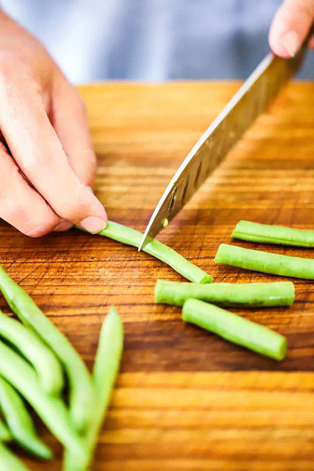 One hand holding a fresh green bean on a cutting board while the other hand uses a large knife to cut it in half.