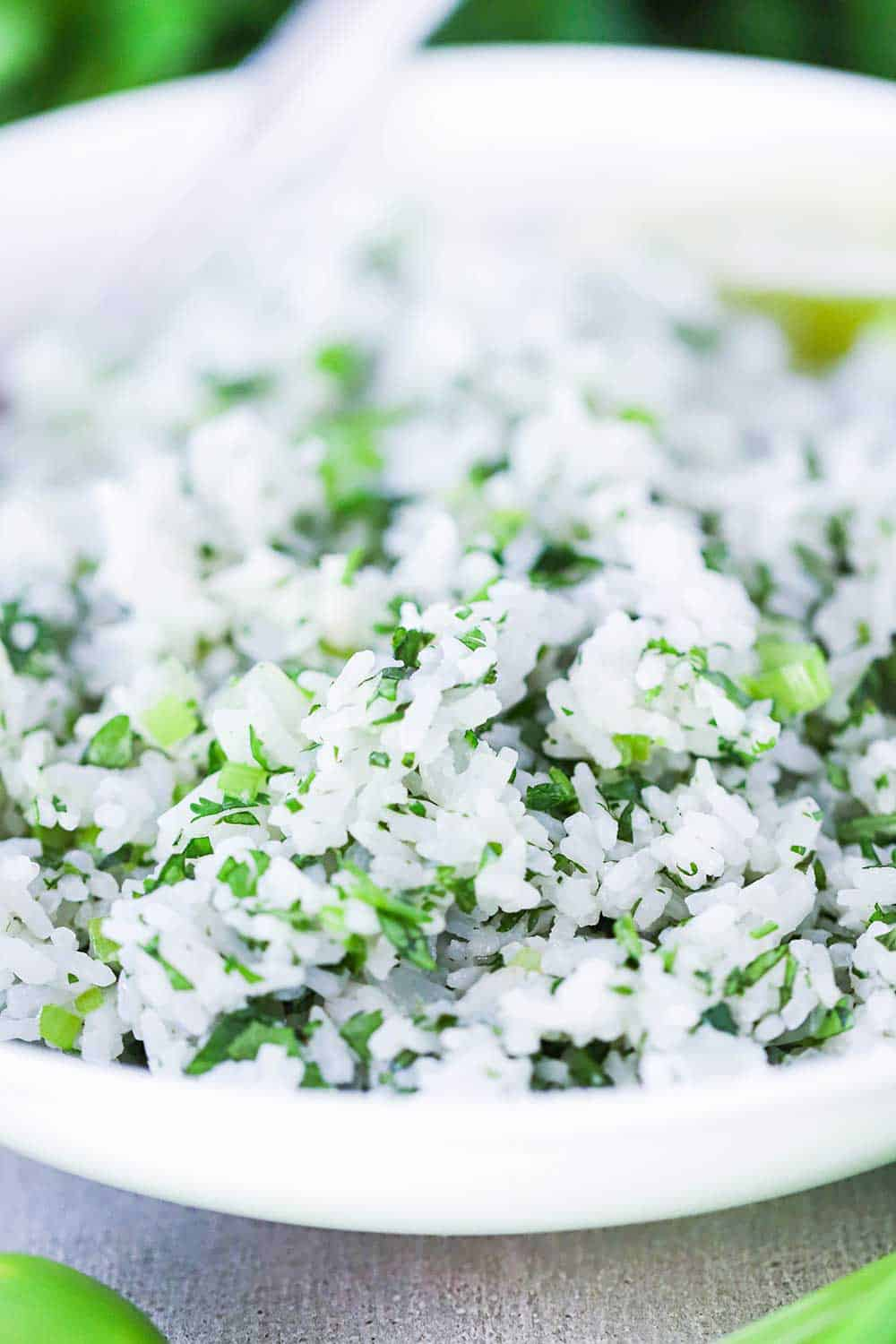 A close-up view of a white bowl filled with Cilantro Lime Rice with a silver spoon in it.