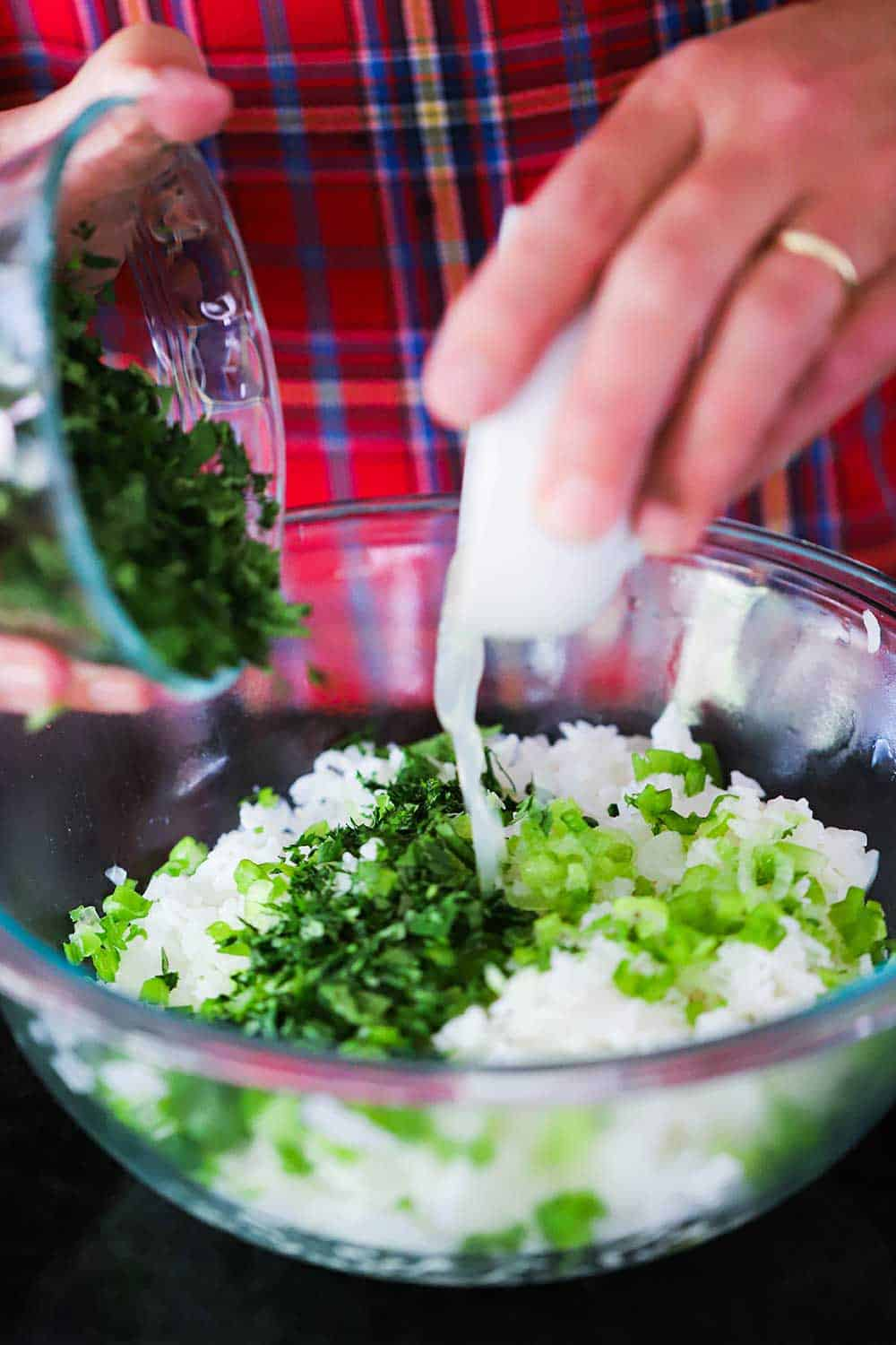 Two hands pouring chopped cilantro and fresh lime juice into a bowl filled with cooked rice and chopped scallions.