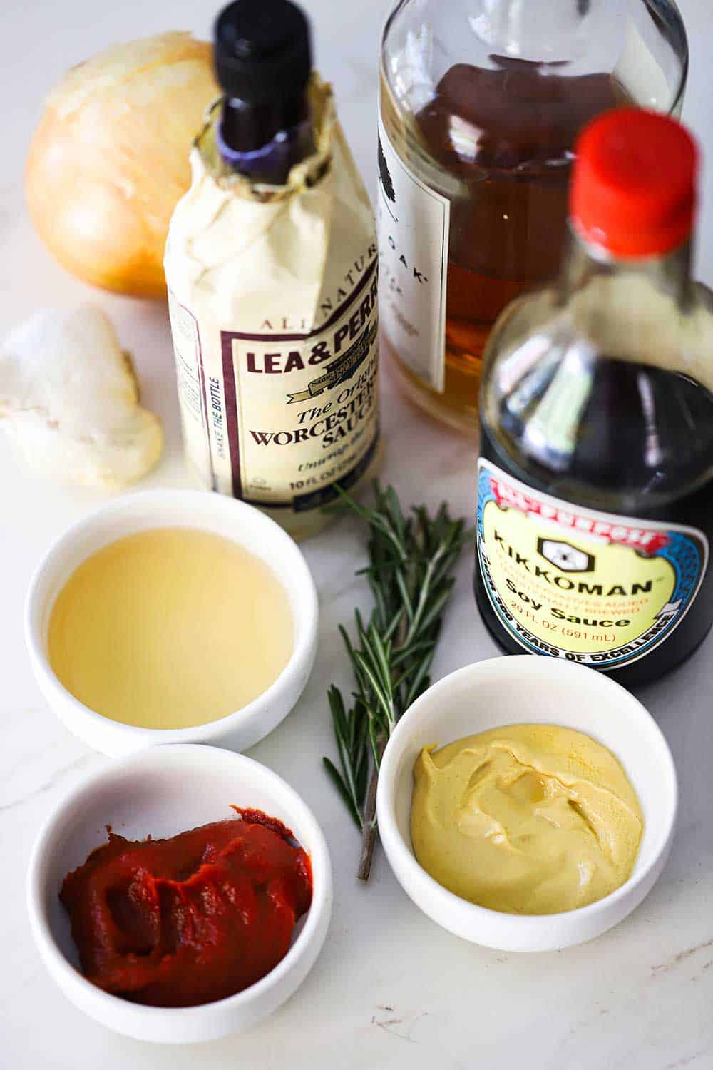 The ingredients for steak sauce including bowls of tomato paste, mustard, vinegar and bottles of soy sauce and Worcestershire