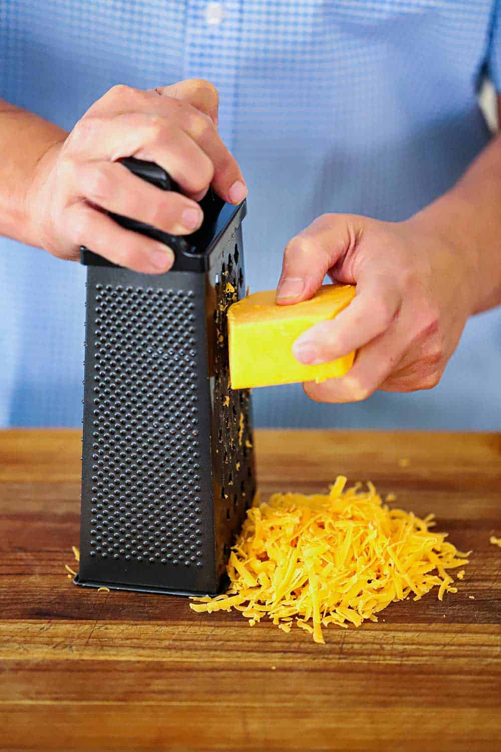 A hand shredding a block of cheddar cheese on a box grater.