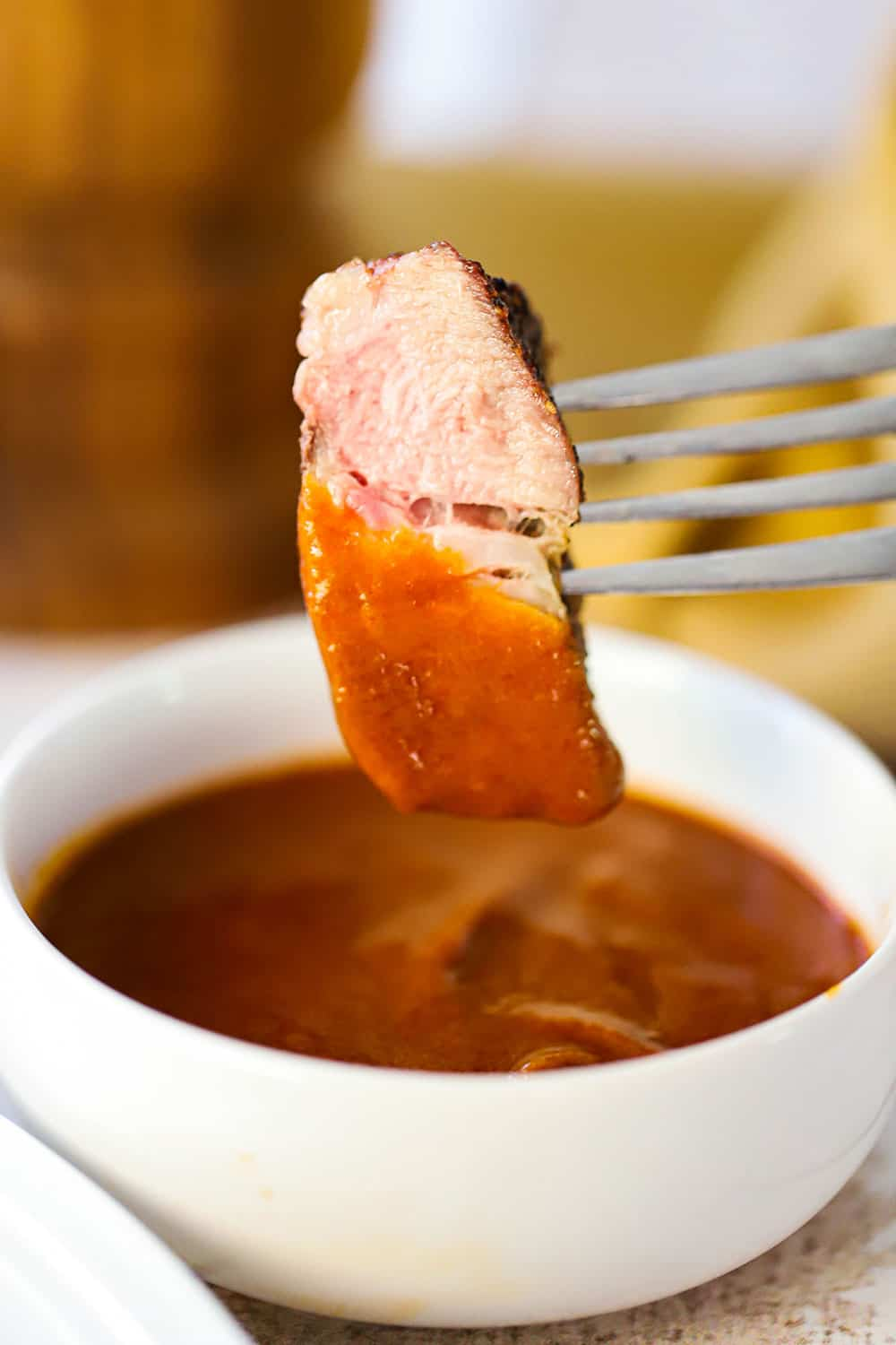 A fork with a slice of pork steak stuck into that is over a small white bowl of steak sauce that it has been dipped into.
