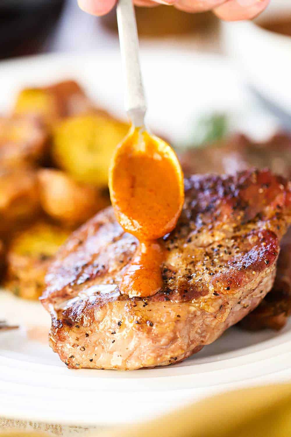 A hand holding a small spoon with steak sauce on it drizzling over a pork steak on a white plate next to roasted potatoes.