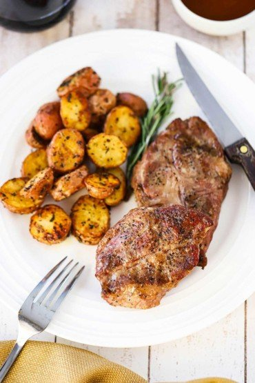 An overhead view of a white dinner plate with a grilled Delmonico pork steak on it next to a sprig of rosemary and roasted new potatoes.