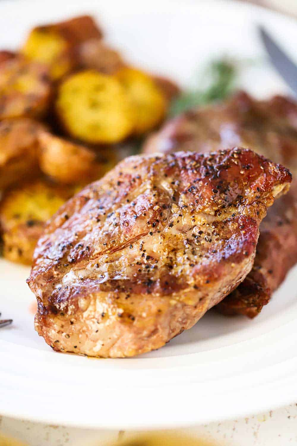 A close up view of a grilled Delmonico pork steak on a white plate next to roasted potatoes.