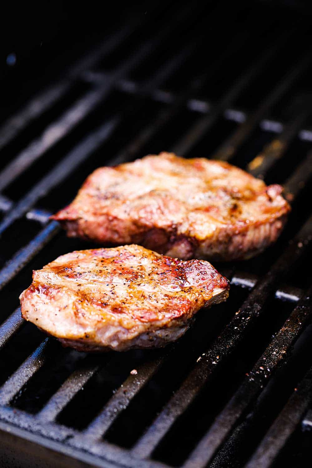 Two pork steaks on a gas grill seasoned with salt and pepper.