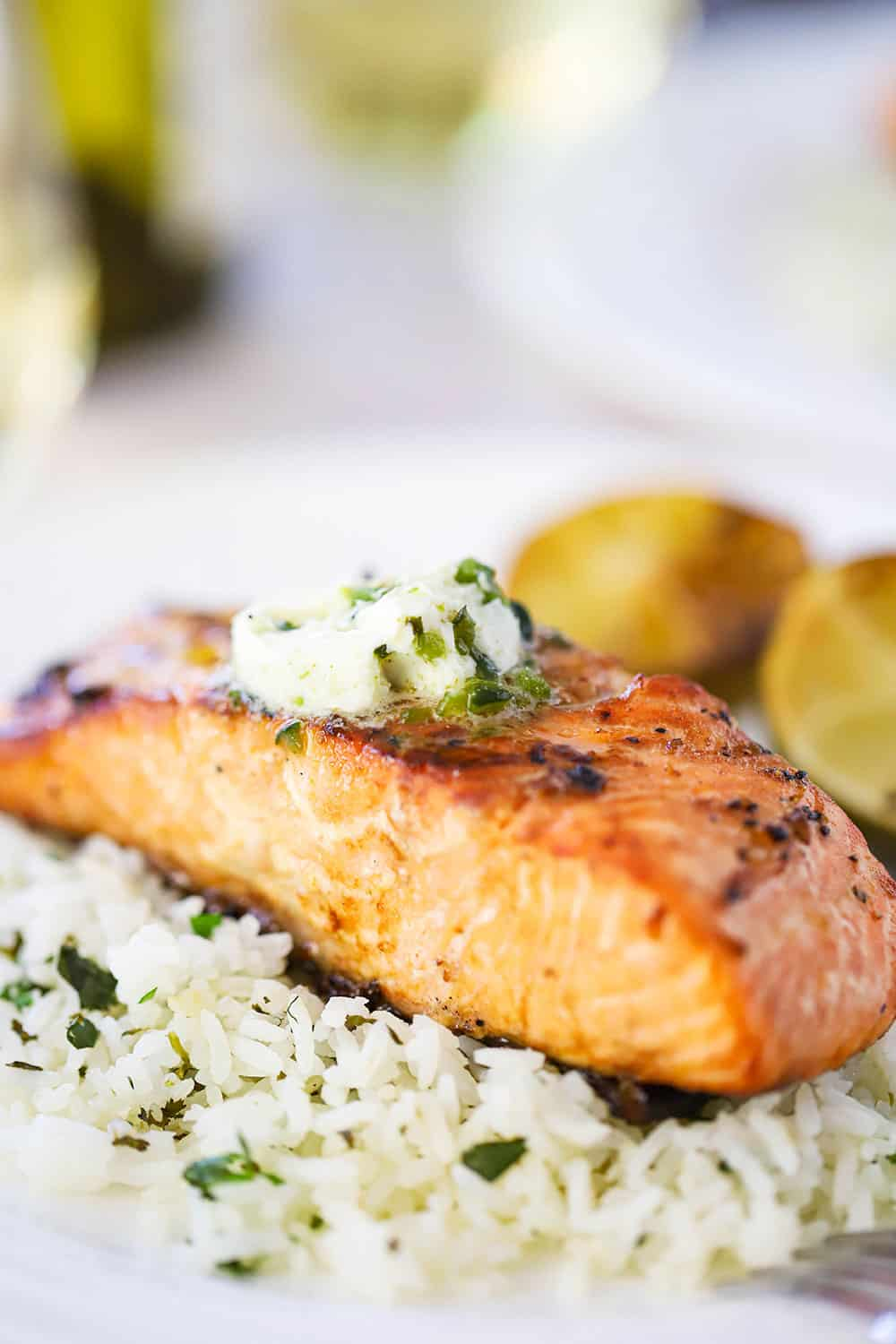 A close up view of a fillet of grilled salmon topped with a pad of melting poblano butter sitting on a bed of cilantro rice on a white plate.