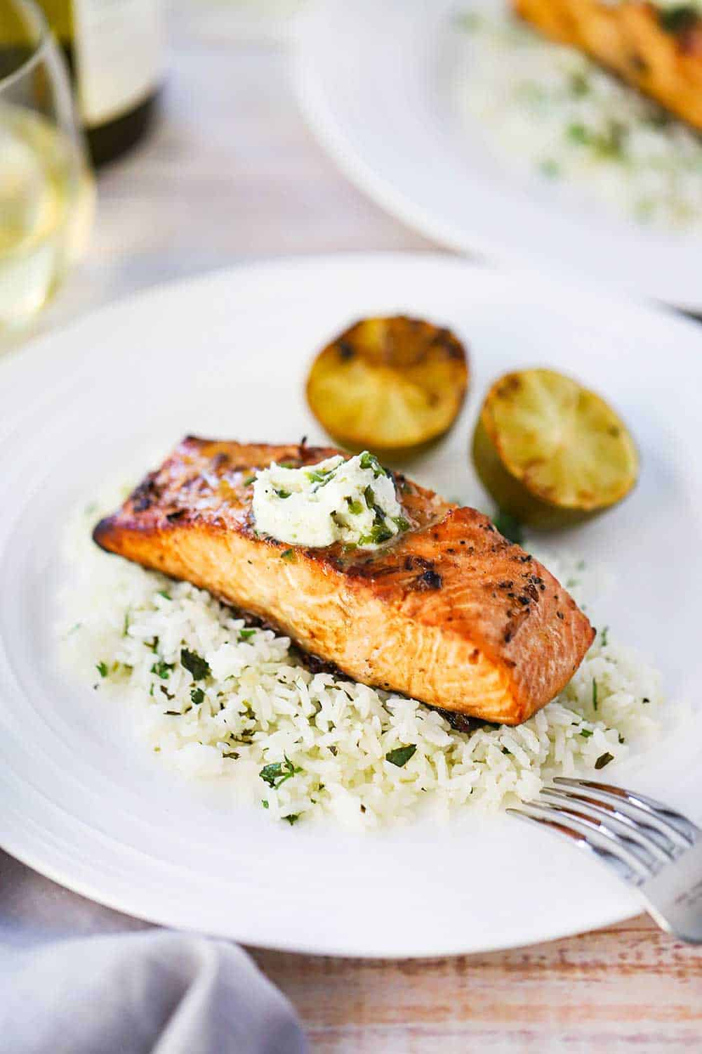 A grilled salmon fillet sitting on top of a bed of cilantro rice with poblano compound butter melting on top of the dish with two grilled limes halves nearby.