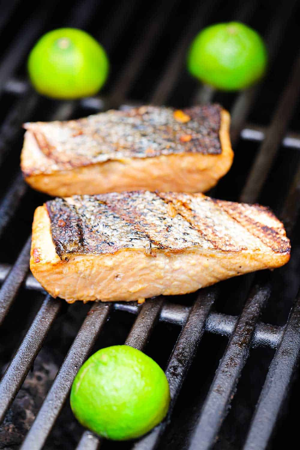 Two salmon fillets on a gas grill with three lime halve on the grill, cut-side down.