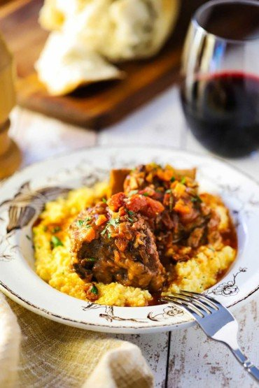 An antique bowl filled with polenta and topped with braised Italian short ribs next to a glass of red wine.