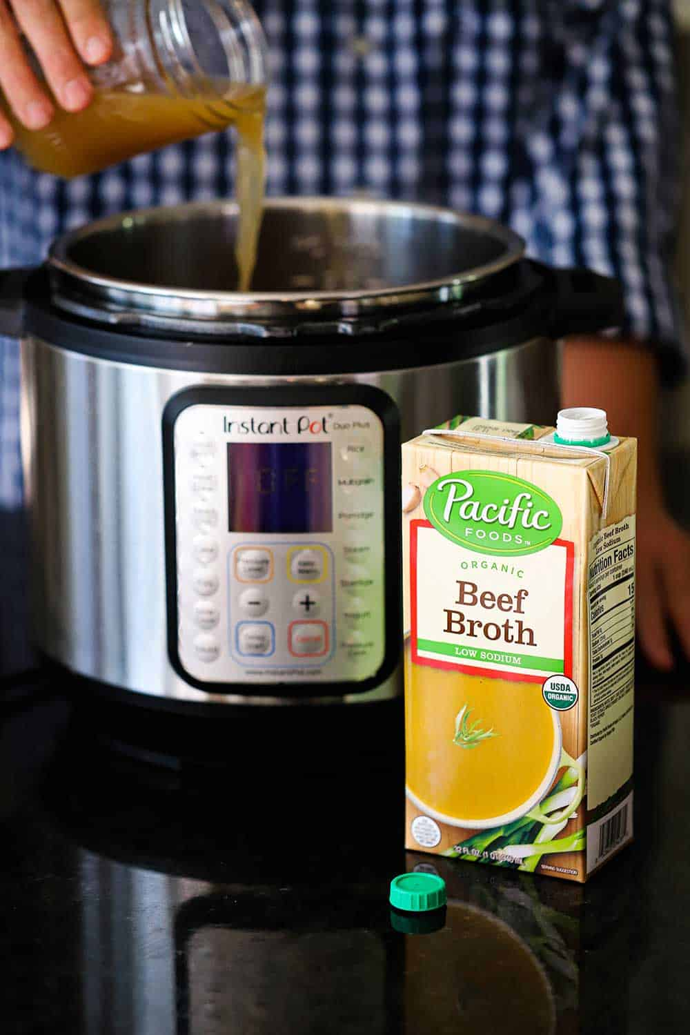 A person pouring beef broth from a jar into an Instant Pot with a box of the broth in front.