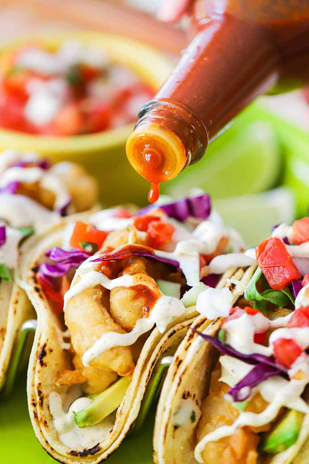 A close up view of a bottle of hot sauce drizzling sauce over Baja fish tacos.