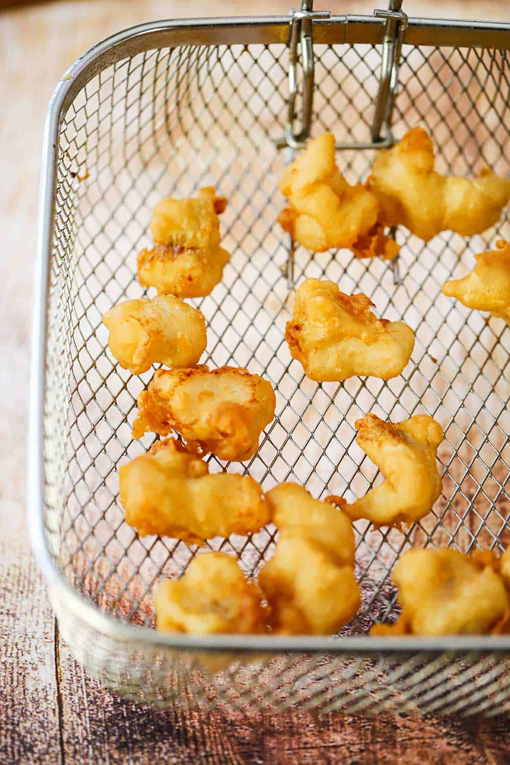 An overhead view of a deep fryer basket filled with golden pieces of fried cod