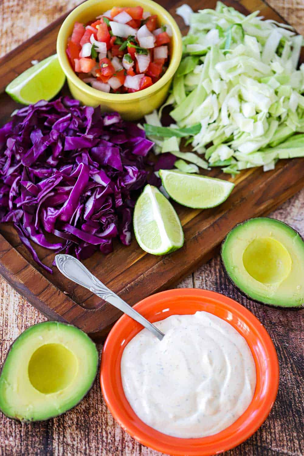 An overhead view of a bowl of Baja sauce, sliced avocados, chopped cabbage, lime wedges, and pico de gallo.