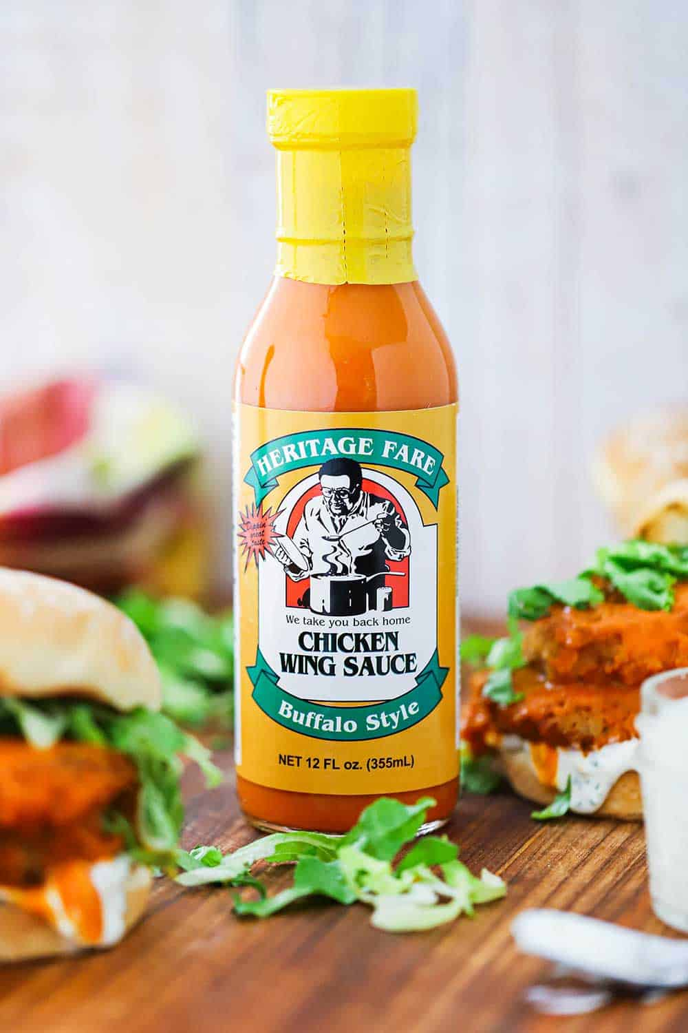 A bottle of Heritage Fare Buffalo Chicken Wing sauce next to a buffalo chicken sandwich on a cutting board.