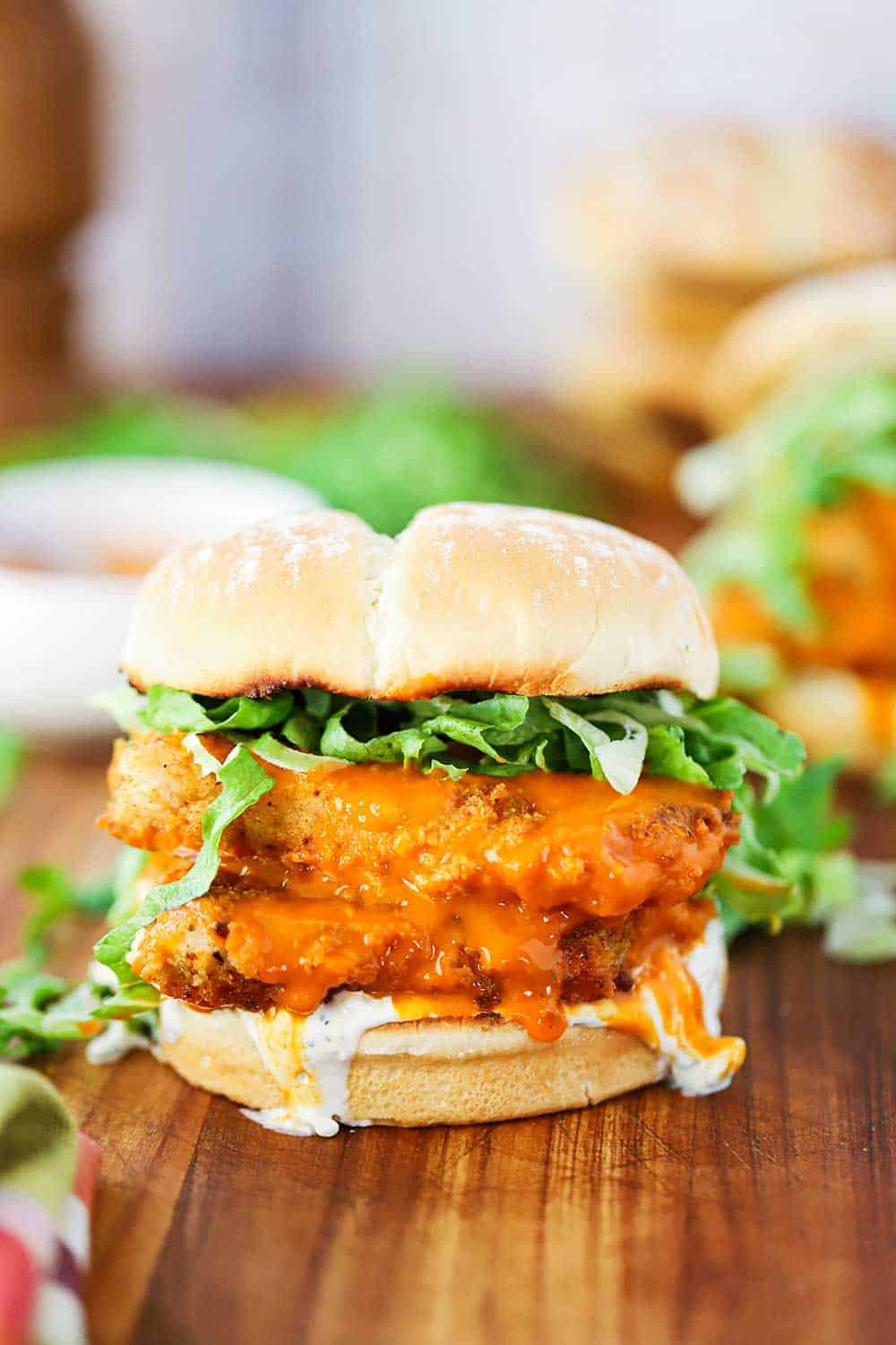 A buffalo chicken sandwich on a wooden board with blue cheese dressing dripping off the side.