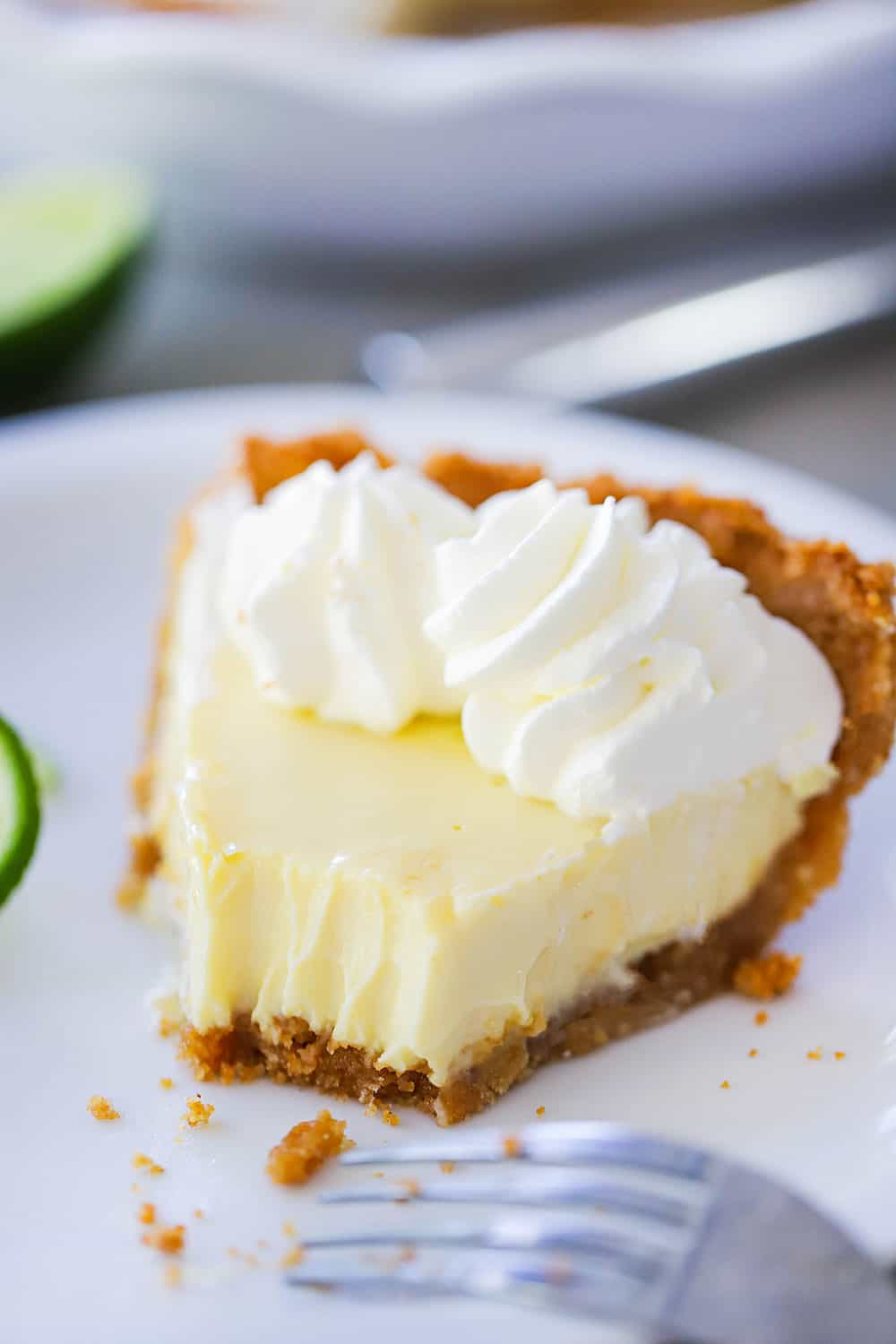 A close-up view of a slice of key lime pie on a plate with a bite taken out of it.