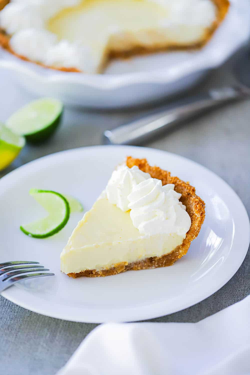 A individual slice of key lime pie on a white plate with a curled lime slice next to it.