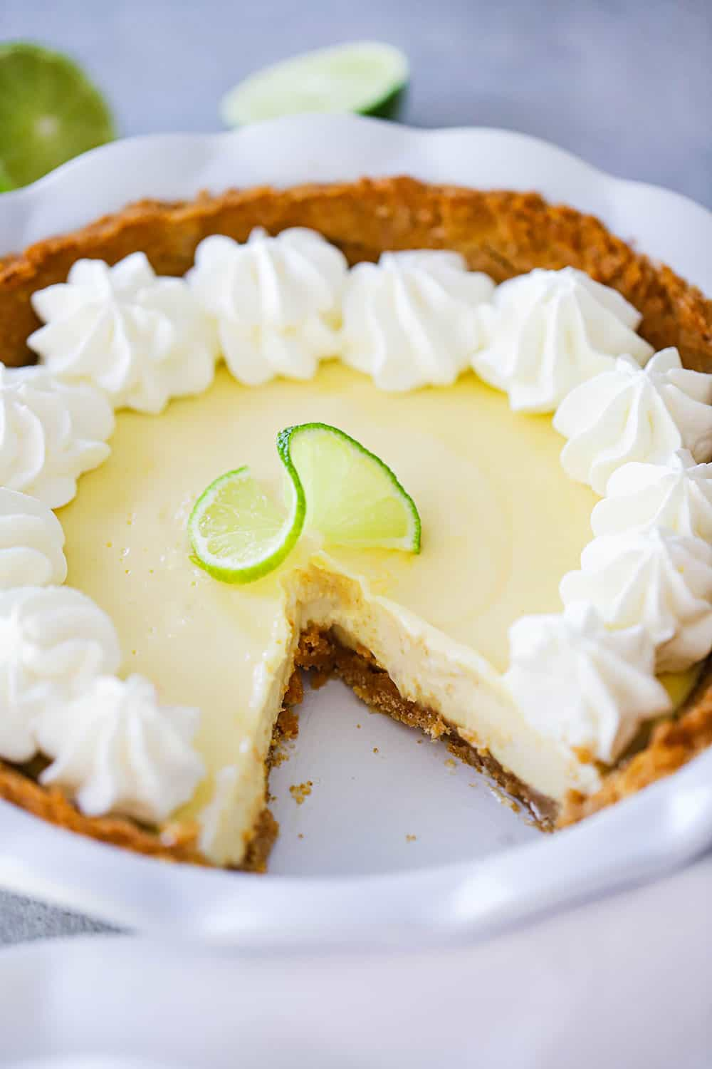 A key lime pie in a white pie dish with a slice cut out of it.