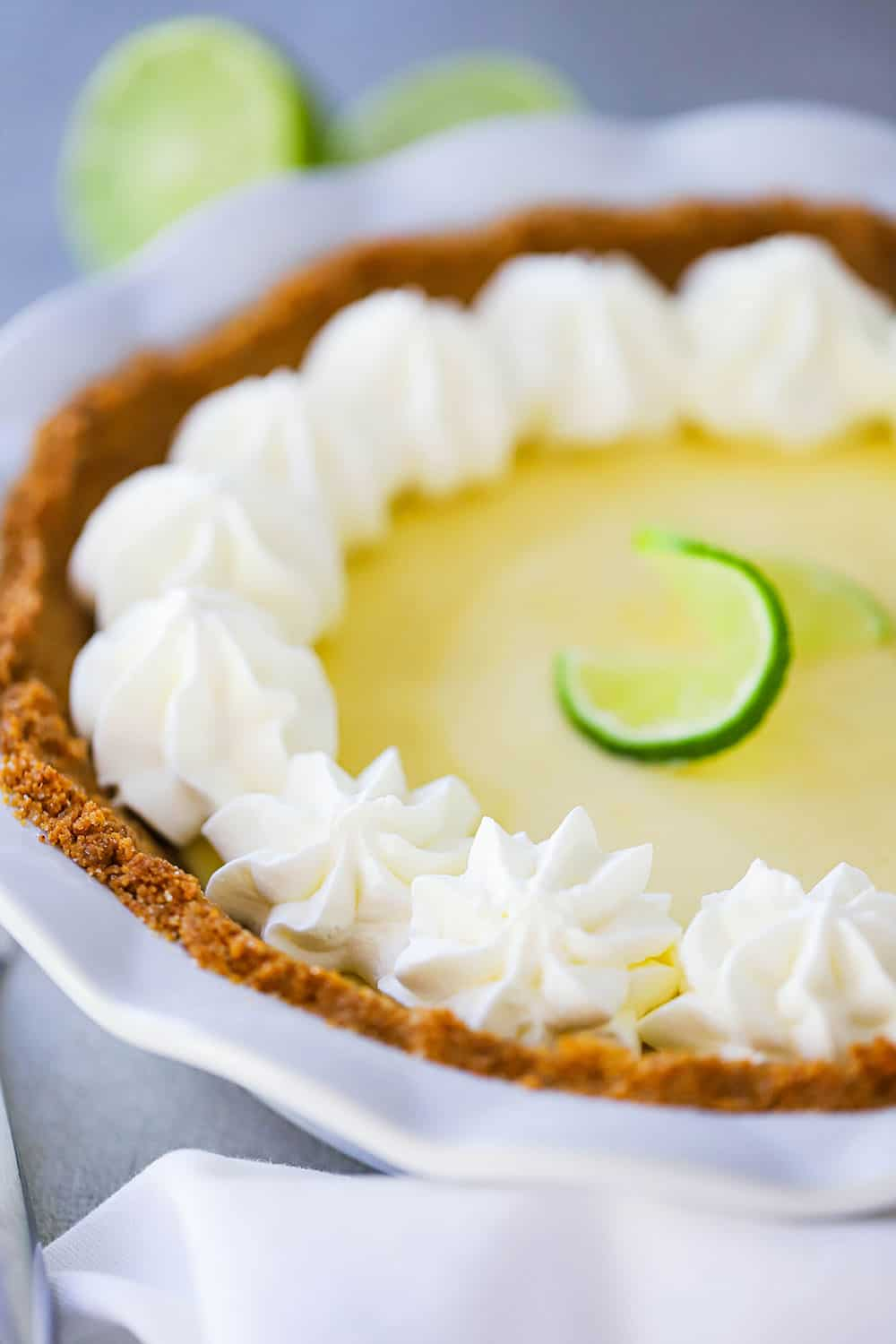 A close-up view of a key lime pie with whipped cream puffs along the edge of the pie.