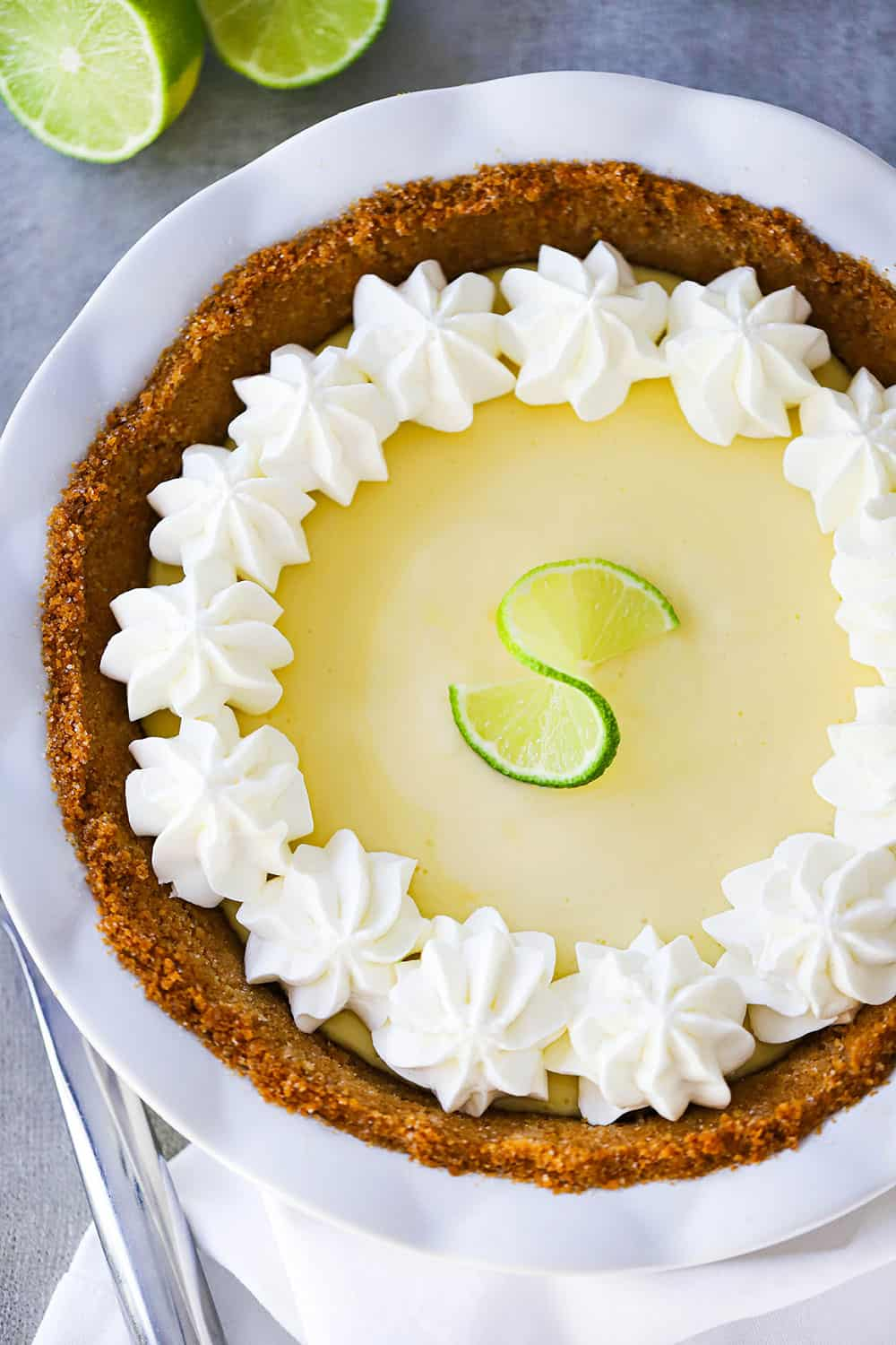 An overhead view of a key lime pie with whipped cream puffs along the edge of the crust.