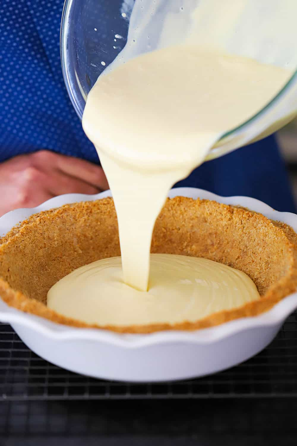 Pie batter being poured out of a glass bowl into a pie dish lined with graham cracker crust.