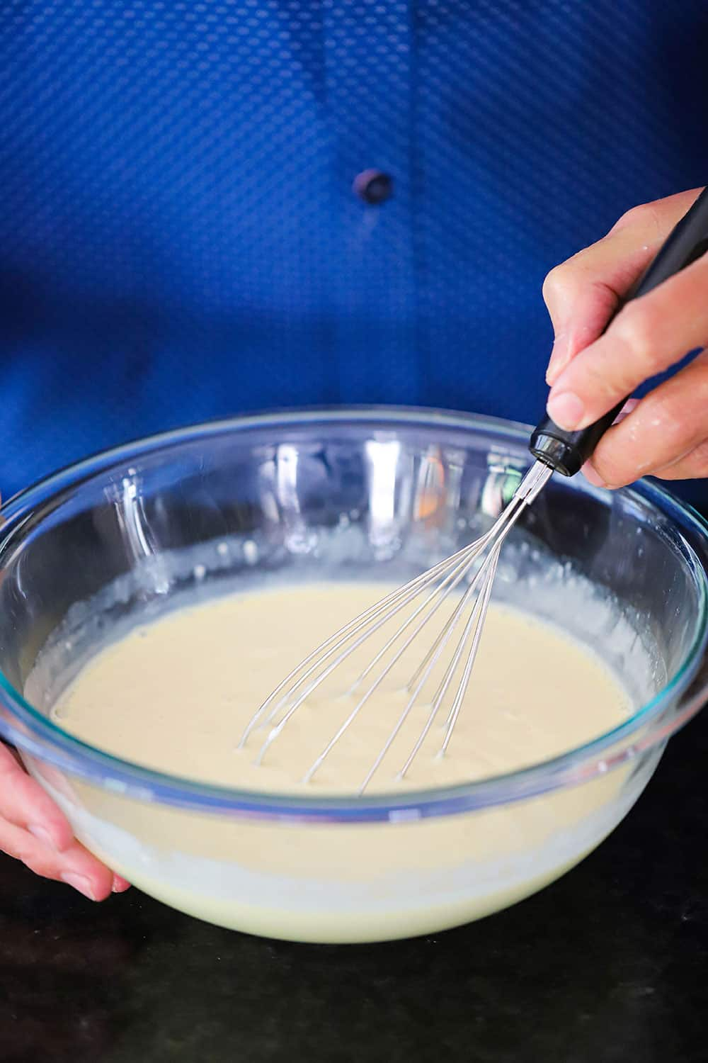 A hand holding a whisk in a glass bowl filled with key lime pie batter.