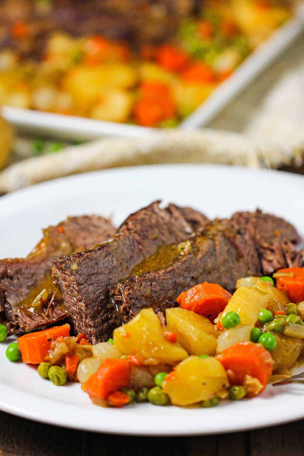 A plate of sliced pot roast next to cooked potatoes, carrots, and peas.